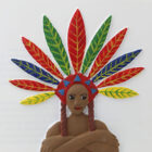Tactile of Grace with arms folded, wearing a large head-dress of red, green, blue and yellow feathers