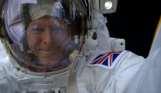Selfie photograph of Tim Peake in white spacesuit and helmet.