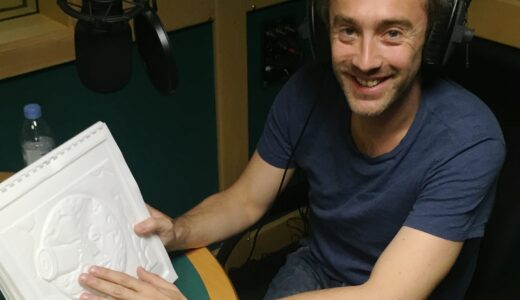 Man in Studio smiling at the camera whilst feeling the thermoform of a planet with a telescope