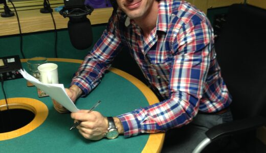 Man in a chequered shirt and wearing  headphones in a recording studio holding on to a script