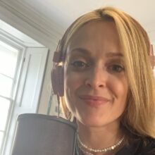 Fearne smiling and in front of her microphone wearing headphones.