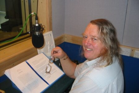 Man smiling back to the camera with a script read to read in front of him