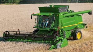 Bright green combine harvester in the centre of a field of corn, ploughing the land.