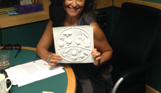 Woman holding up a thermoform of a healthy eating plate with a smile on her face