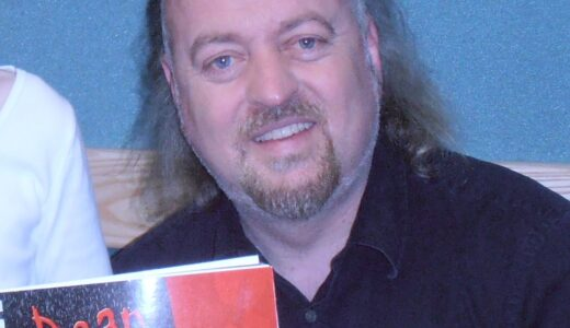 Bill Bailey, holding up a copy of Dear Vampa and smiling.