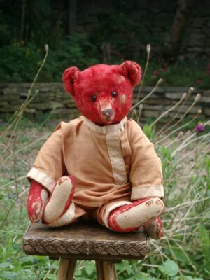 Red Steiff bear seated on wicker chair in cottage garden.