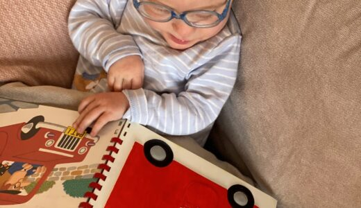 A toddler boy on the sofa with an open book showing a tactile picture of a red postal van.