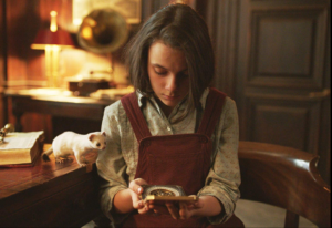 Inside a library or study room a girl holds a round compass like object whilst a small white animal looks at what she is holding.
