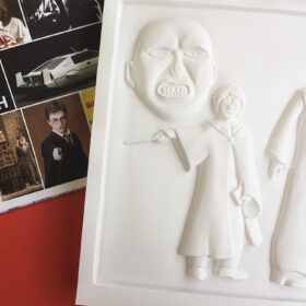 Tactile picture of Harry Potter dressed in his school uniform and gown an holding his wand.