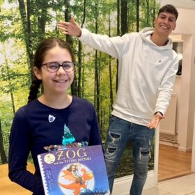 Imogen holding a copy of Zog and the Flying Doctors with Richie Driss in the background smiling.