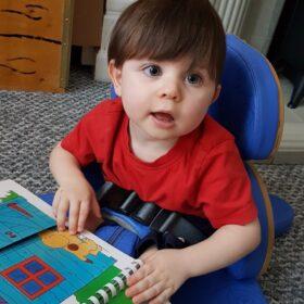 A toddler boy feeling a lift the flap book.