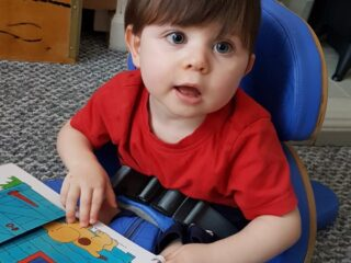 A toddler boy feeling a lift the flap book.
