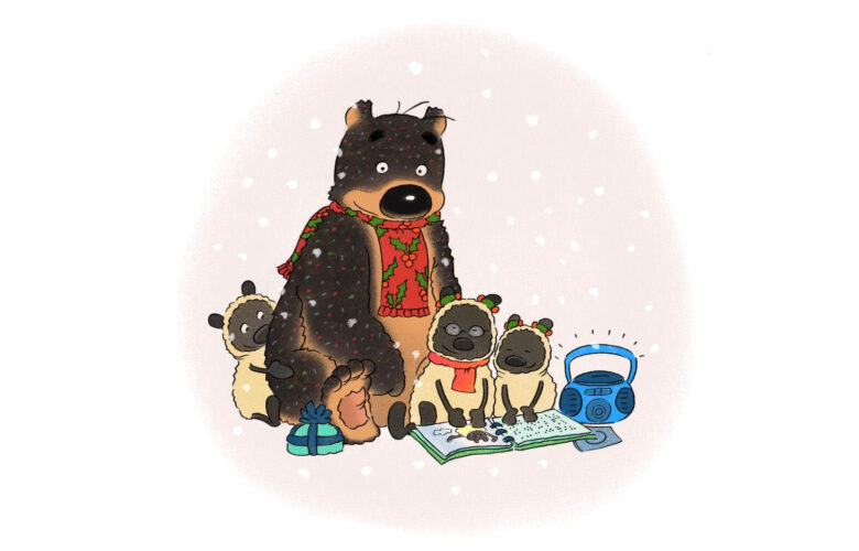 Hugless Douglas the Bear sitting on the snow wearing a festive scarf whilst reading and listening to an audio book with his friends the sheep.