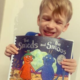 Jacob smiles and holds up a Touch to See adaptation of the Smeds and the Smoos