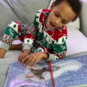 Jai reading and feeling The Snowman, smiling.