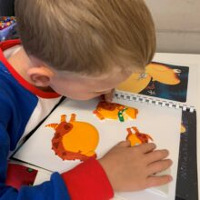 Jacob feeling the pictures of a dinosaur eating the moon.