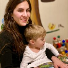 Alba with her son, facing the camera and smiling, with a book on their lap.