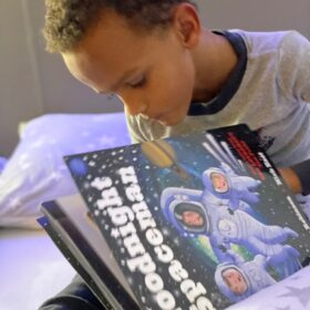 Jain turning the pages of Goodnight Spaceman
