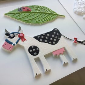 A close up shot of a painted tactile picture showing a ladybird on a leaf and a black and white cow.