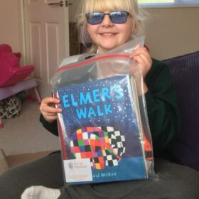 Mid-length shot of a little girl with blonde hair, smiling and holding up the picture book Elmer's Walk.