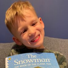 Smiling boy holding a copy of The Snowman.
