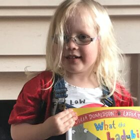Matilda holding up a copy of What the Ladybird Heard and wearing a ladybird jacket.