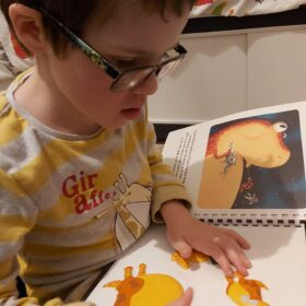 Tobias feeling the tactile pictures in The Dinosaur That Pooped a Planet.