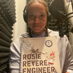 A close up shot of Angela holding a copy of Rosie Revere Engineer and in her home studio.