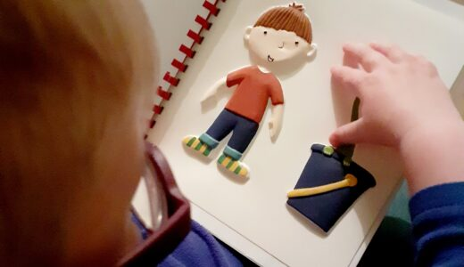 A boy feeling the tactile picture of Harry from Harry and the Dinosaurs.