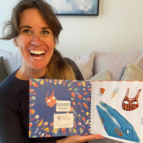 The author, Sarah, holding up Living Paintings tactile adaptation of her book Somebody Swallowed Stanley