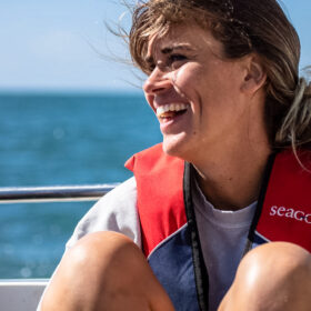 Close up photo f sarah Roberts smiling and sitting on a boat.