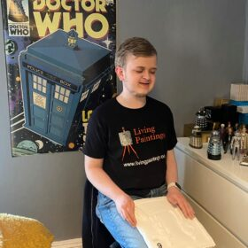 Louis sitting on a chair in front of a Doctor Who poster and holding a tactile picture.