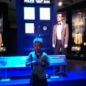 Louis as a little boy at a Doctor Who exhibition standing in front of the Tardis and Matt Smith