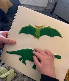 A child's little hand feeling a dinosaur.