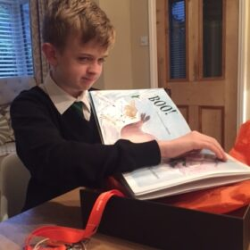 A young boy feeling the book The Bear Who Went Boo