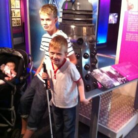 Louis as a boy standing in front of a Dalek.