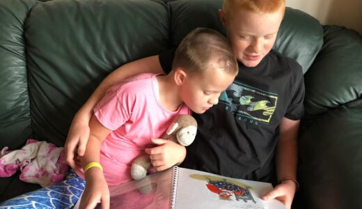Tayen and her brother on a sofa reading a Touch-to-See book.