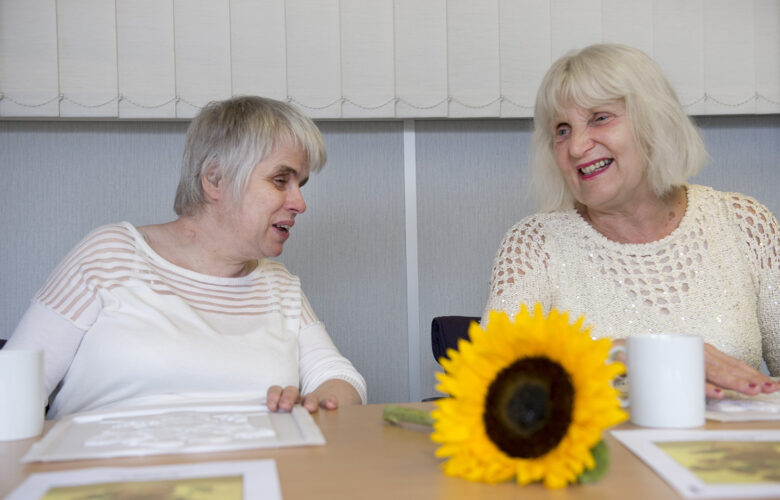 Two ladies sitting next to each other, chatting and smiling.