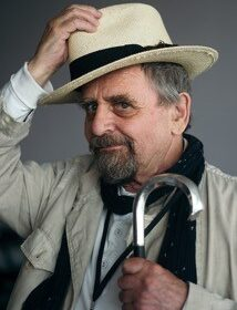 A portrait shot of Sylvester McCoy tipping his hat and carrying an umbrella taken by Simon King.