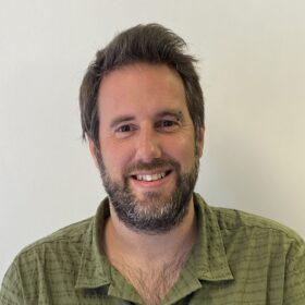 A head and shoulders shot of David smiling and facing the camera, wearing a khaki green shirt and with a short beard.