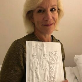 A head and shoulders shot of a smiling Juliet with tactile picture of Emmeline Pankhurst