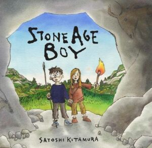 Stone Age Boy written and illustrated by Satoshi Kitamura. A boy and girl standing at the rocky, arched entrance of a cave. Behind them is a vast green plain and rocky hillsides.